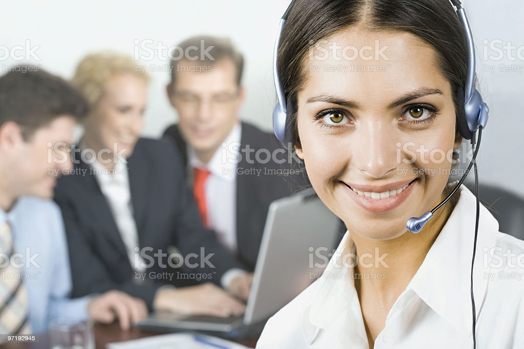 Close-up of woman with headset and three other people stock photo