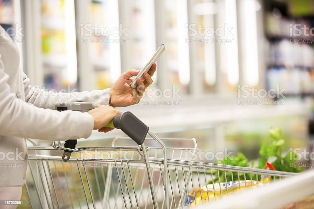 Close-up of woman with trolley and smartphone stock photo