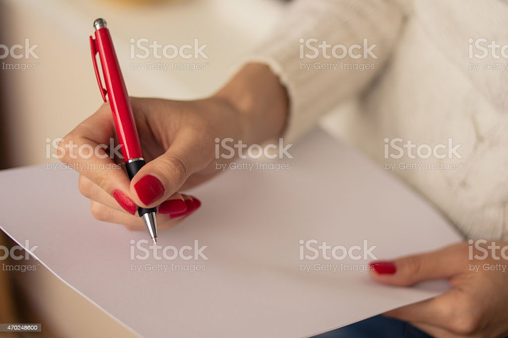 Close-up of woman writing on blank paper stock photo