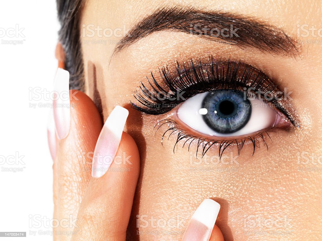 Close-up of woman's eye with nails on face stock photo