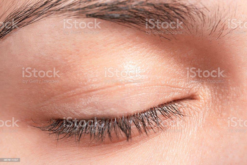 Close-up of woman's eyelid including eyelashes and eyebrow stock photo