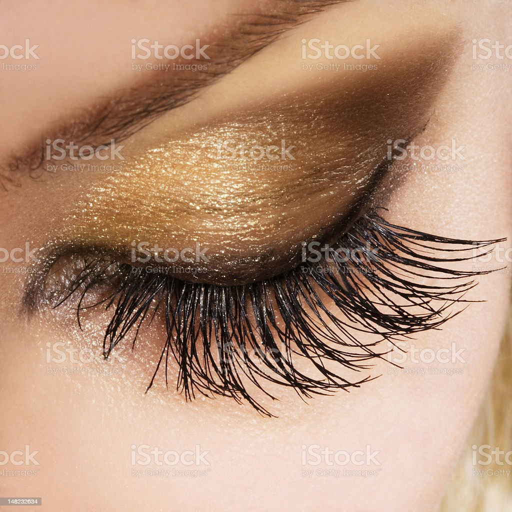 Close-up of woman's eyelid wearing bronze and brown make-up royalty-free stock photo
