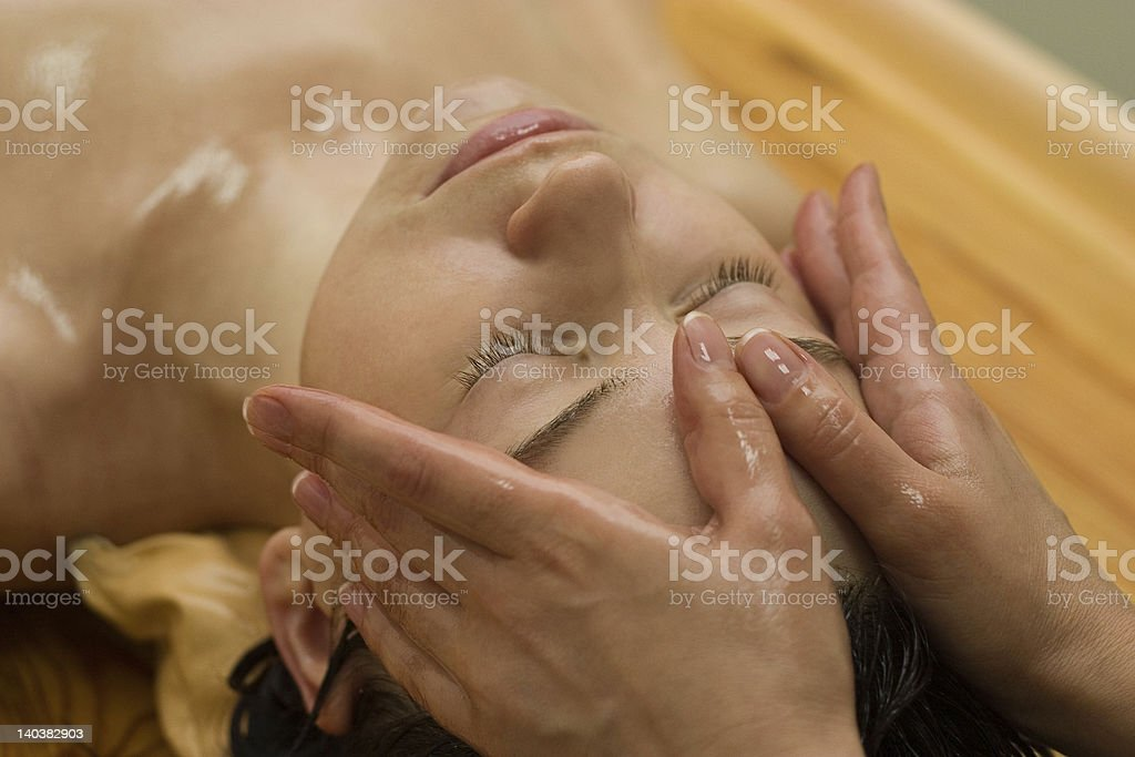 Close-up of woman's face receiving Ayurvedic massage stock photo