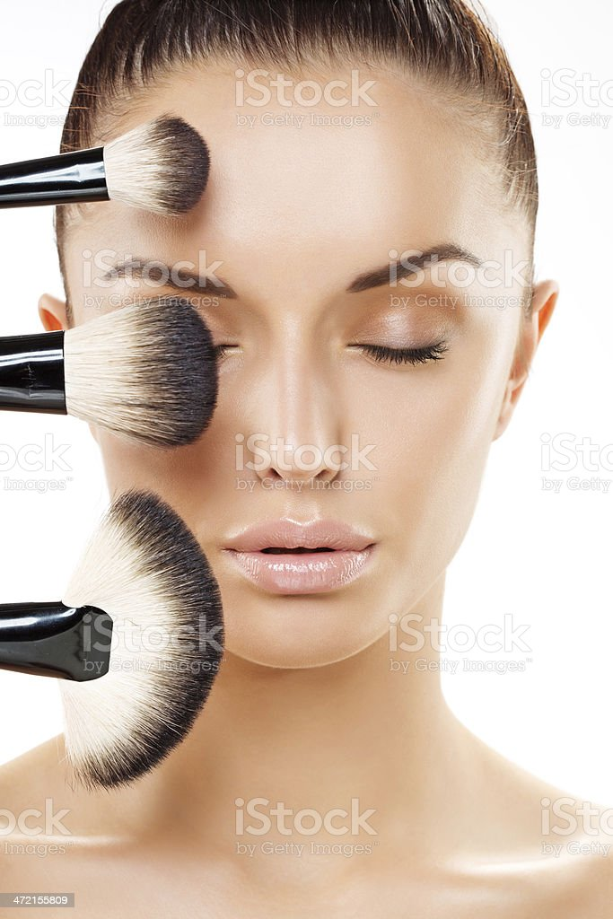 close-up of woman's face with the  make-up brushes at foreground stock photo
