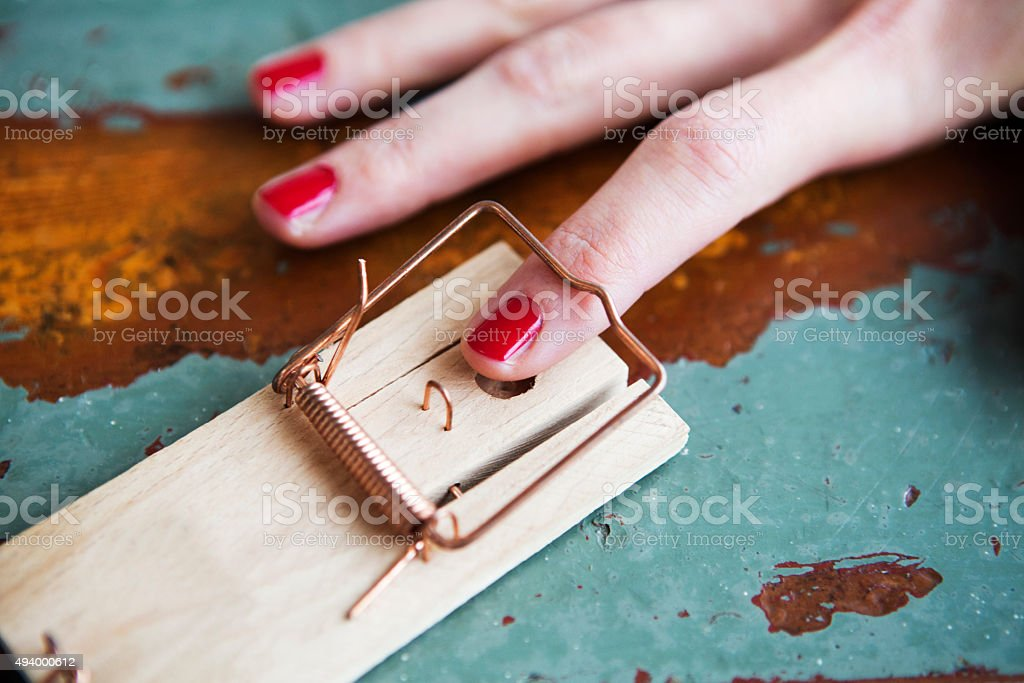 closeup of woman's finger in mousetrap stock photo