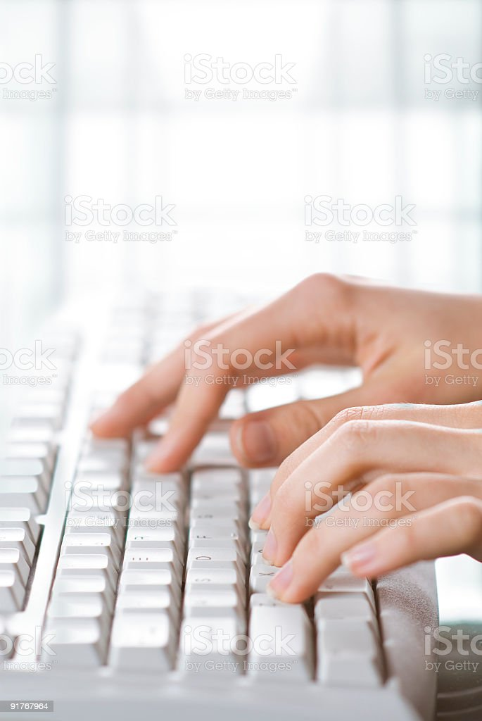 Close-up of woman's fingers typing on white keyboard royalty-free stock photo