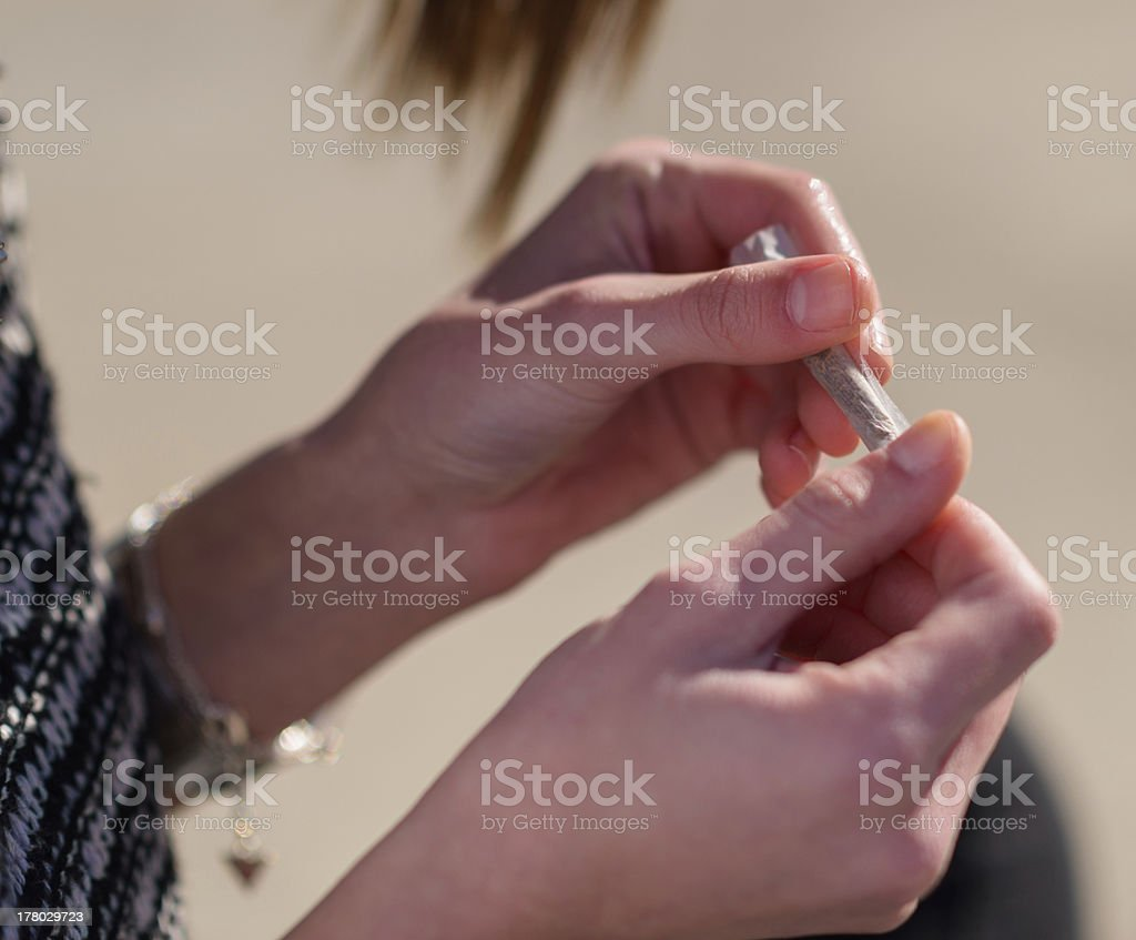 Closeup Of Woman's Hand Rolling Cigarette stock photo