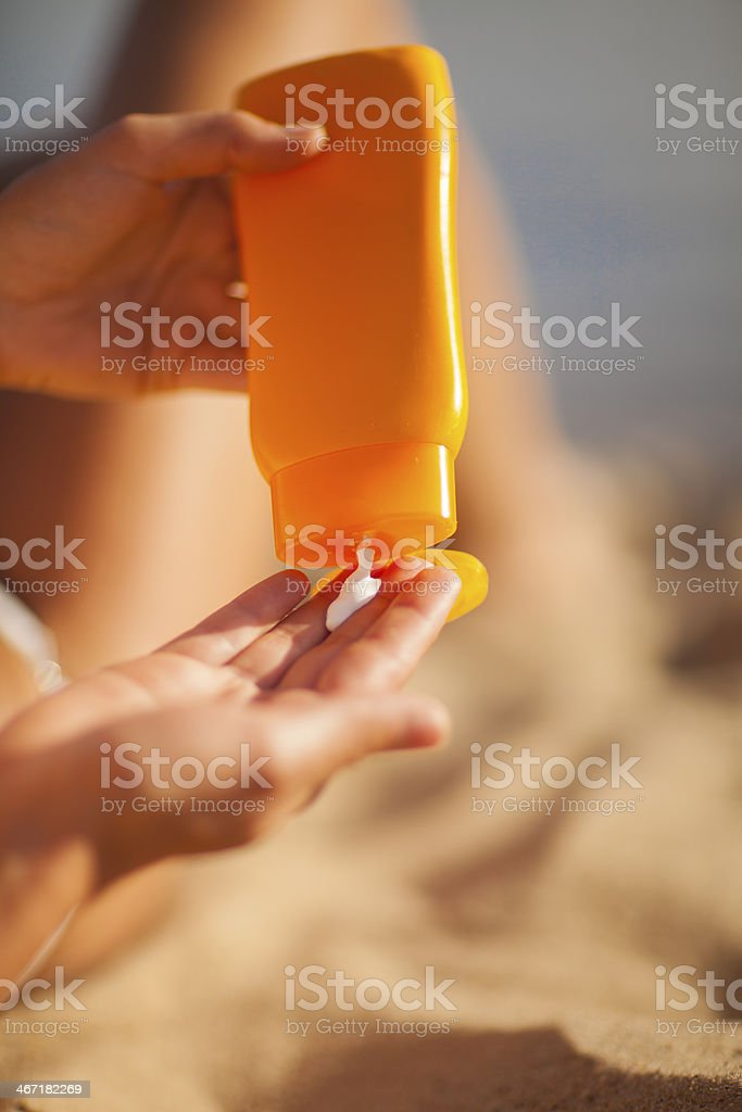Close-up of woman's hand squirting sunscreen lotion stock photo