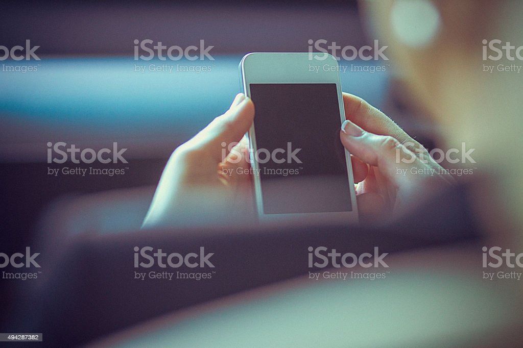 Closeup of woman's hands holding and touching a smartphone, POV stock photo