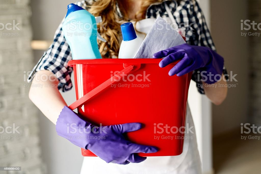 Close-up of woman's hands holding bucket full of cleaners stock photo