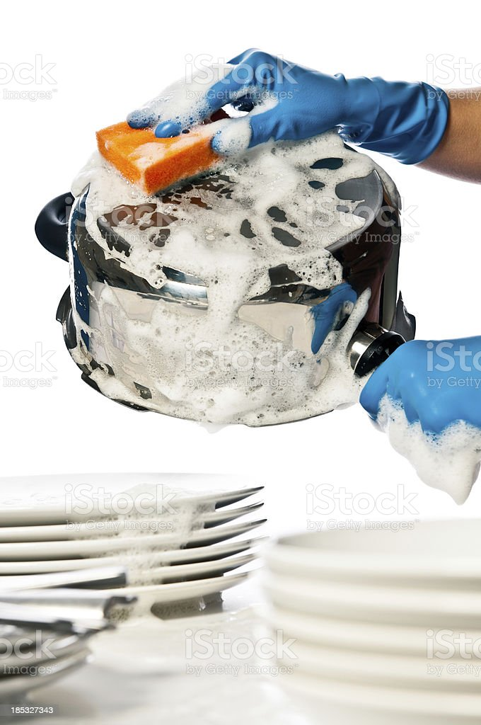 Close-up of woman\'s hands in protective gloves washing dishes and...