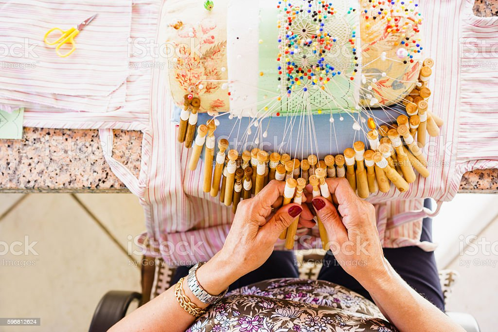 Close-up of woman's hands weaving using bobbins and threads stock photo