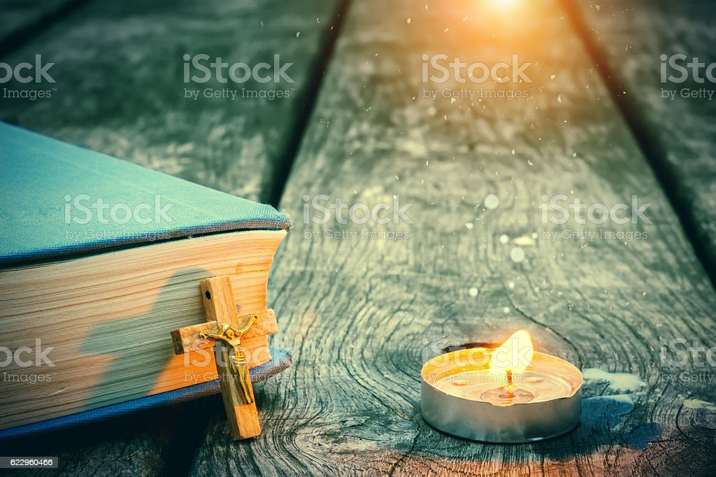 Closeup of wooden Christian cross on bible, burning candle on the old...