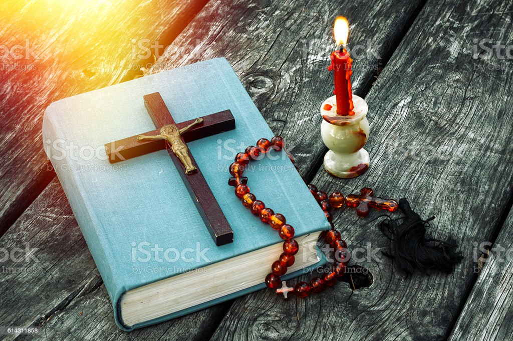 Closeup of wooden Christian cross on bible, burning candle stock photo
