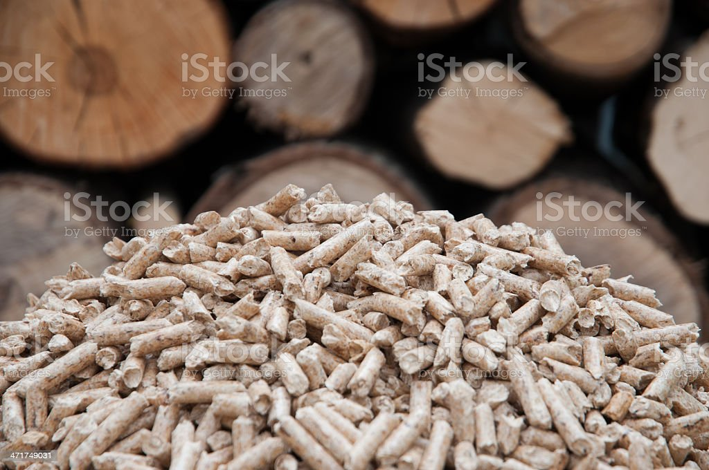 A close-up of wooden pellets with wood logs stock photo