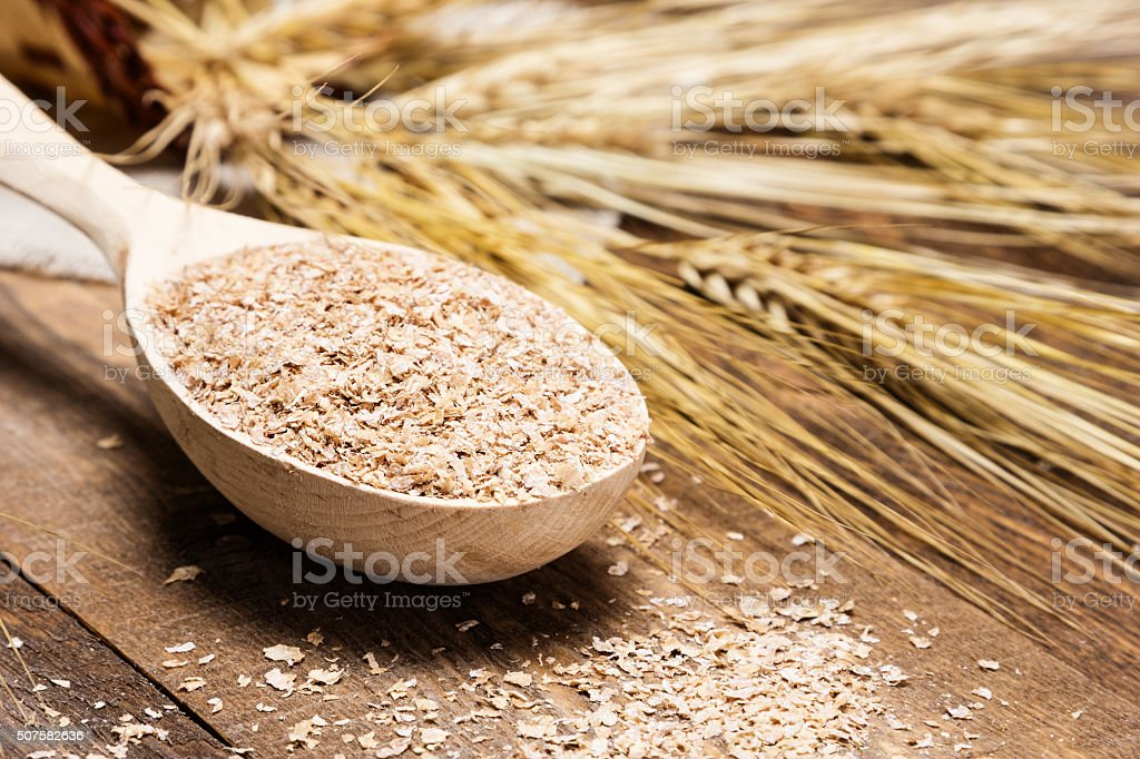 Closeup of wooden spoon filled with wheat bran stock photo