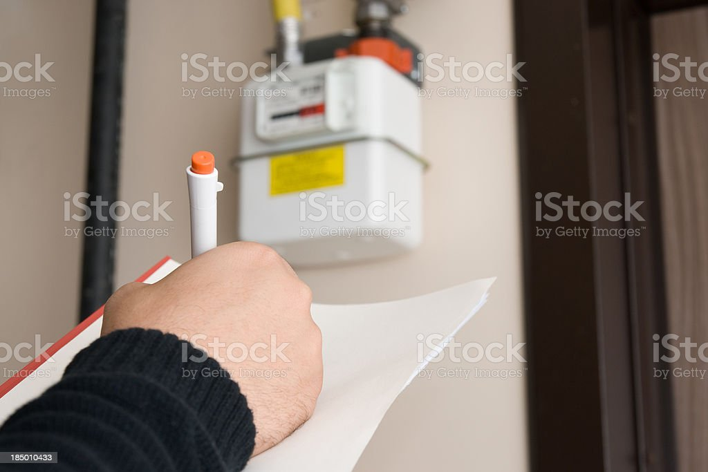 Close-up of worker reading and noting gas mater figure stock photo