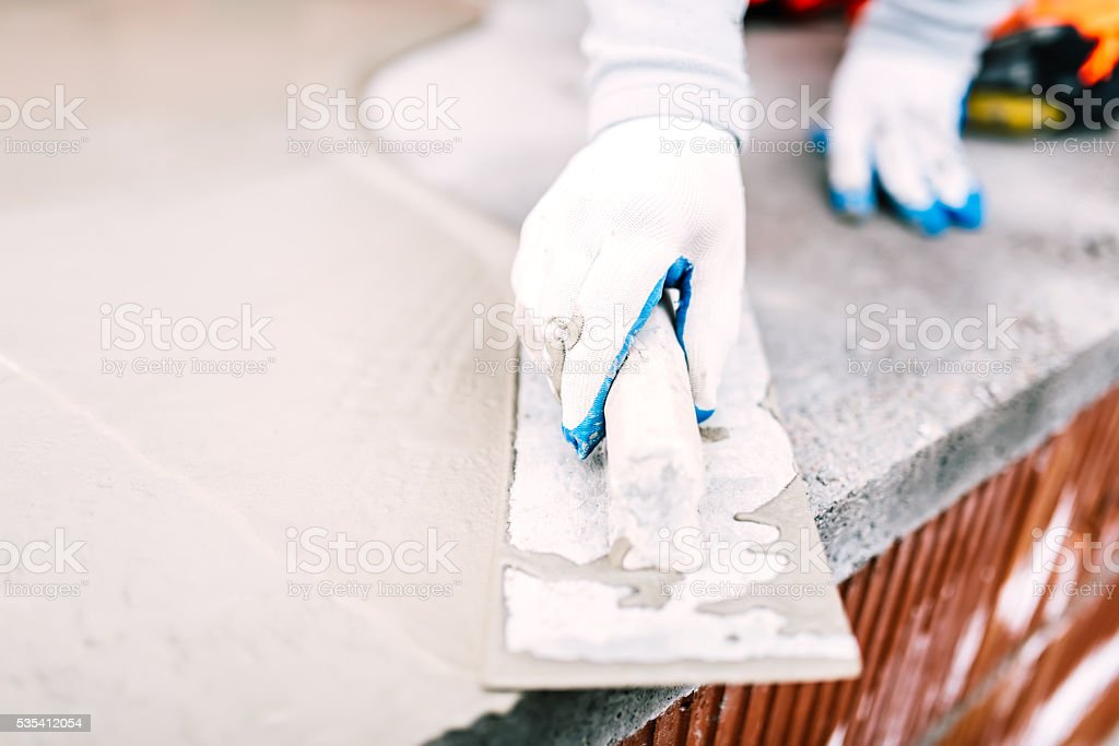 close-up of worker steel trowel and hand, using plastering tools stock photo