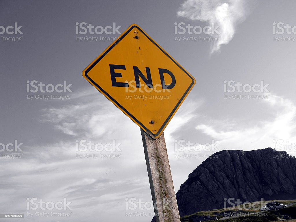 Close-up of yellow END sign against gray sky with mountain stock photo