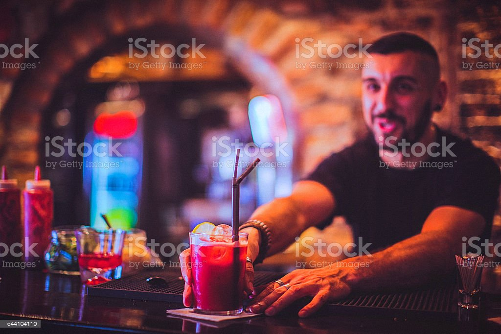 Close-up of young bartender serving cocktail in nightlife bar stock photo
