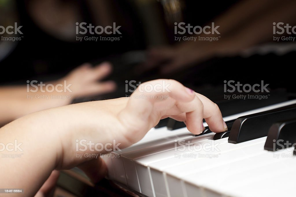 Closeup of young child's hands while playing piano royalty-free stock photo