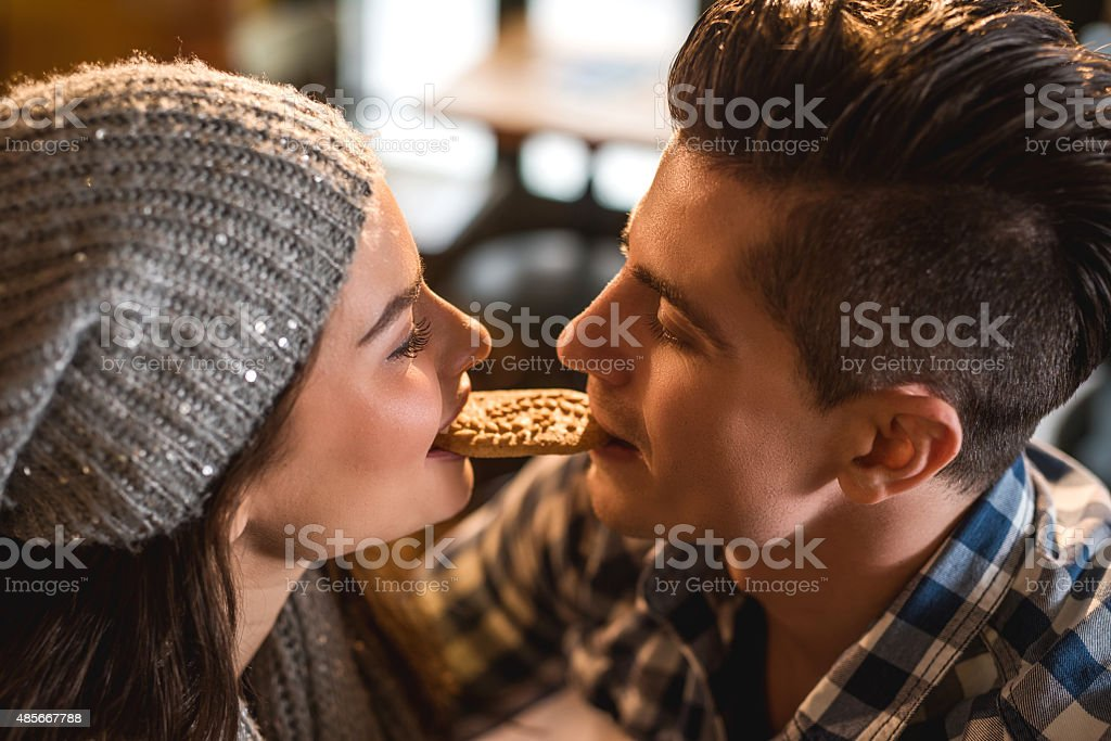 Close-up of young couple eating a cookie in a cafe. stock photo