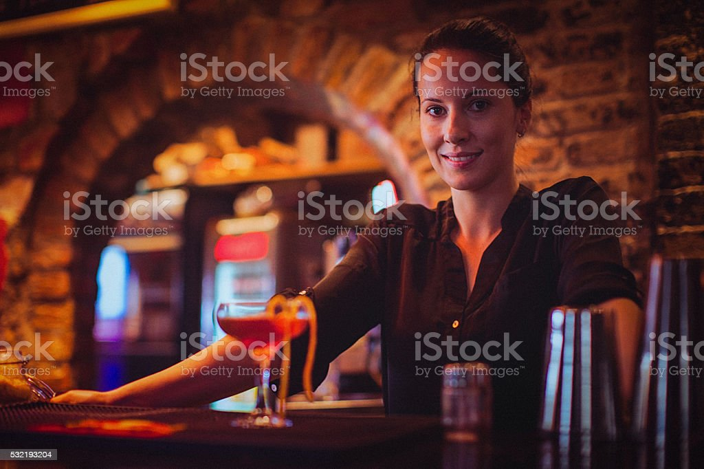 Close-up of young female bartender serving cocktail in cocktail bar stock photo