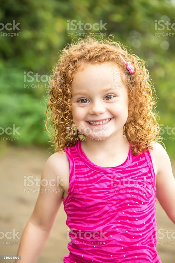 Close-Up of Young Girl With Curly Red Hair stock photo