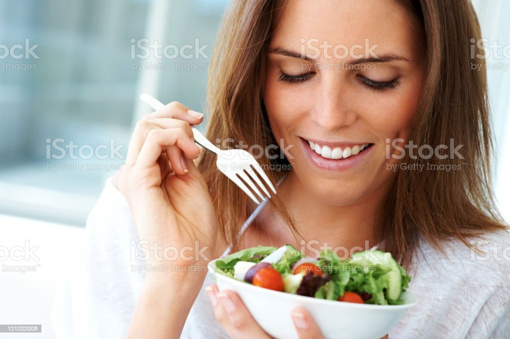 Close-up of young happy woman eating salad royalty-free stock photo