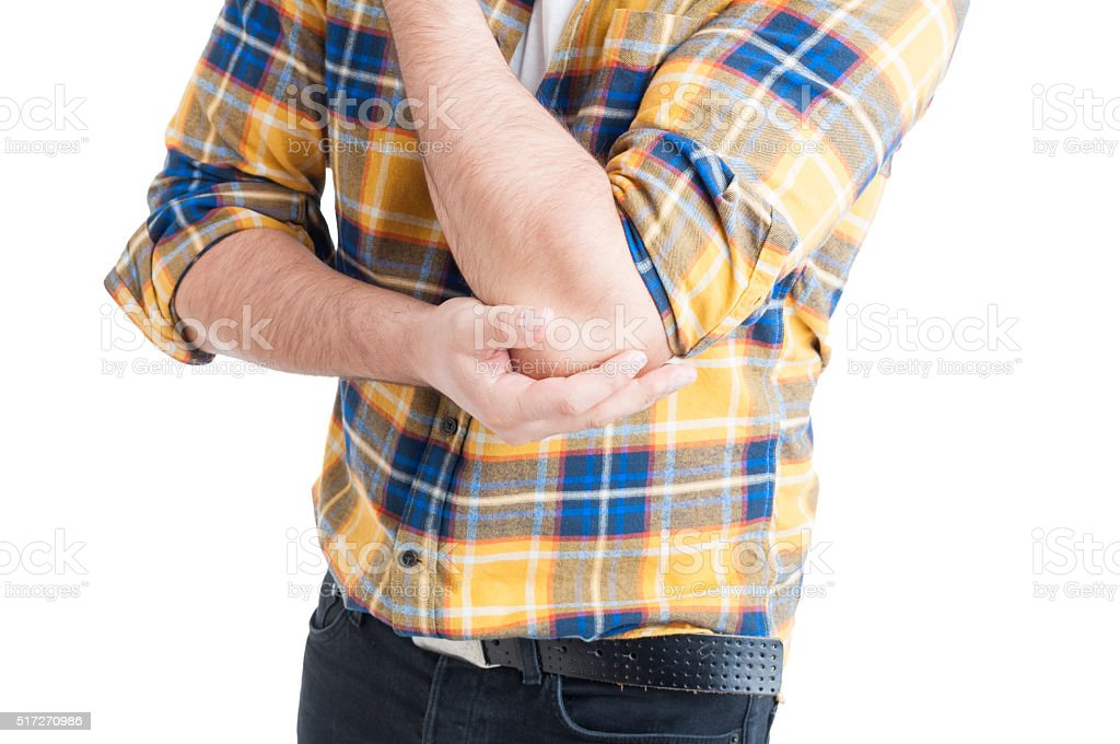 Close-up of young male with pain in injured arm stock photo