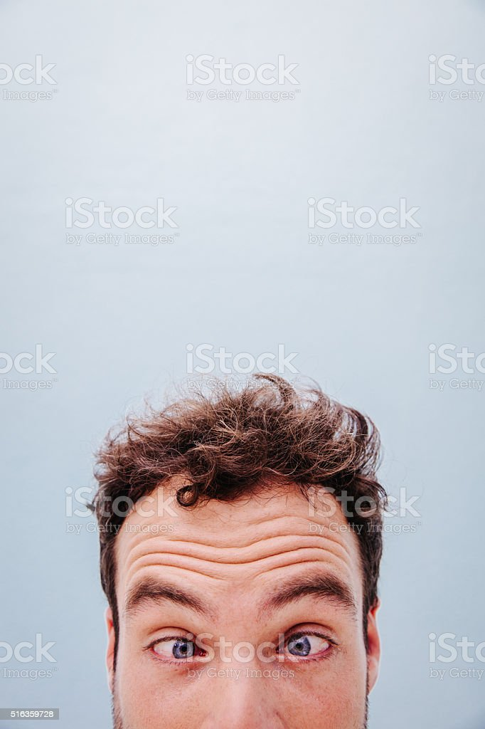 Close-up of Young man looking with crazy eyes stock photo