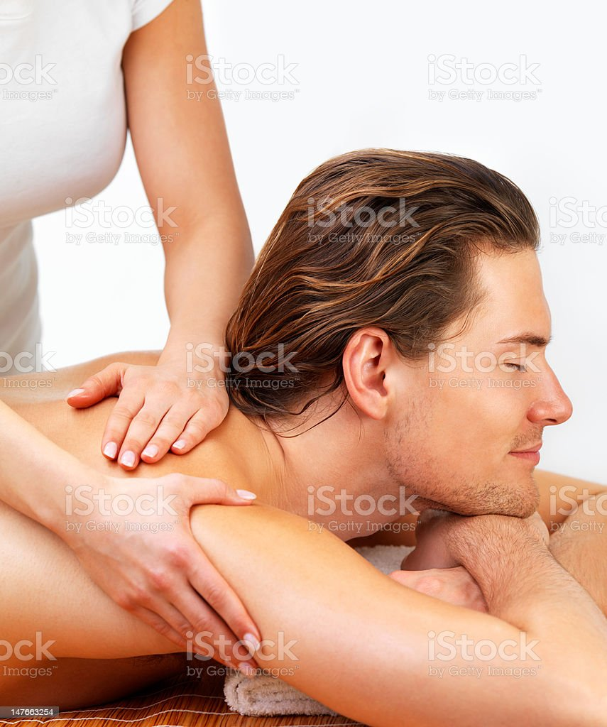 Closeup of young man receiving shoulder massage at day spa royalty-free stock photo