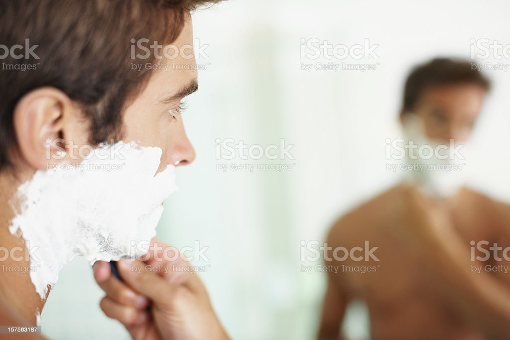 Closeup of young man shaving stock photo