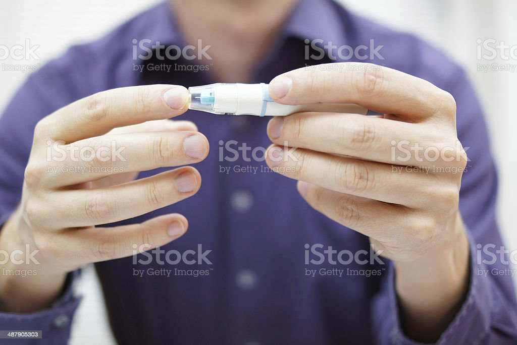 Closeup of young man using checking level of blood sugar stock photo