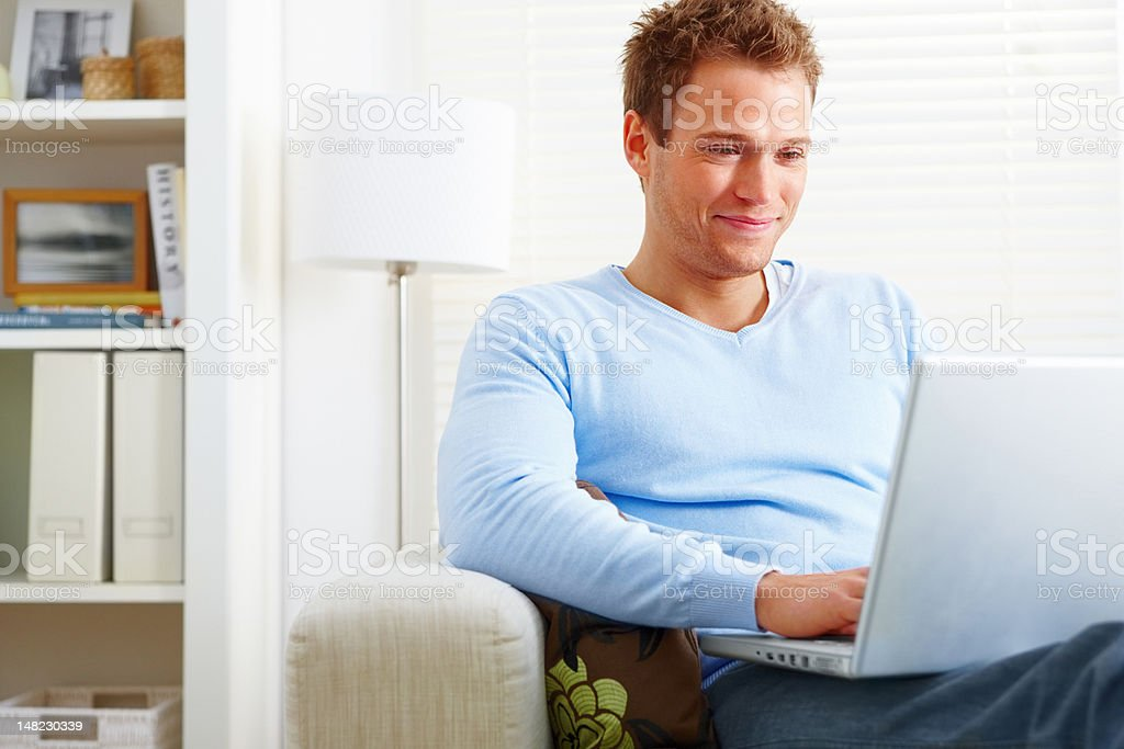 Close-up of young man using laptop and smiling royalty-free stock photo