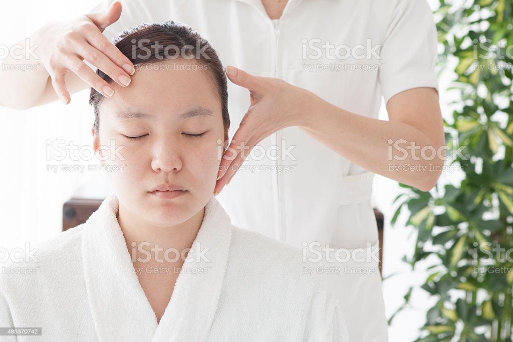 Close-up of young relaxing beautiful woman having facial massage stock photo