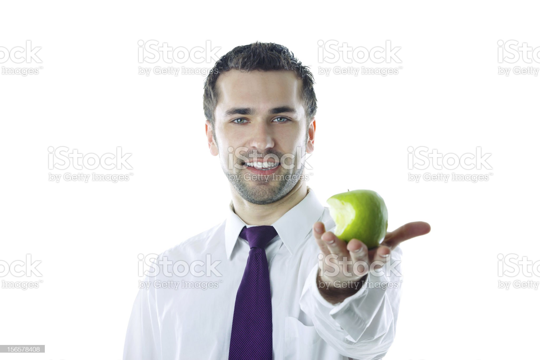 Close-up of  young smiling businessman holding bitten apple royalty-free stock photo