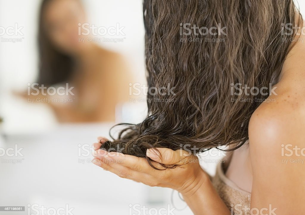 Closeup of young woman applying hair mask stock photo