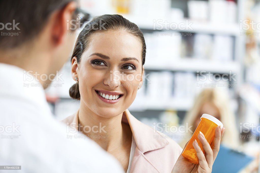 Close-up of young woman holding pill bottle at the pharmacy royalty-free stock photo