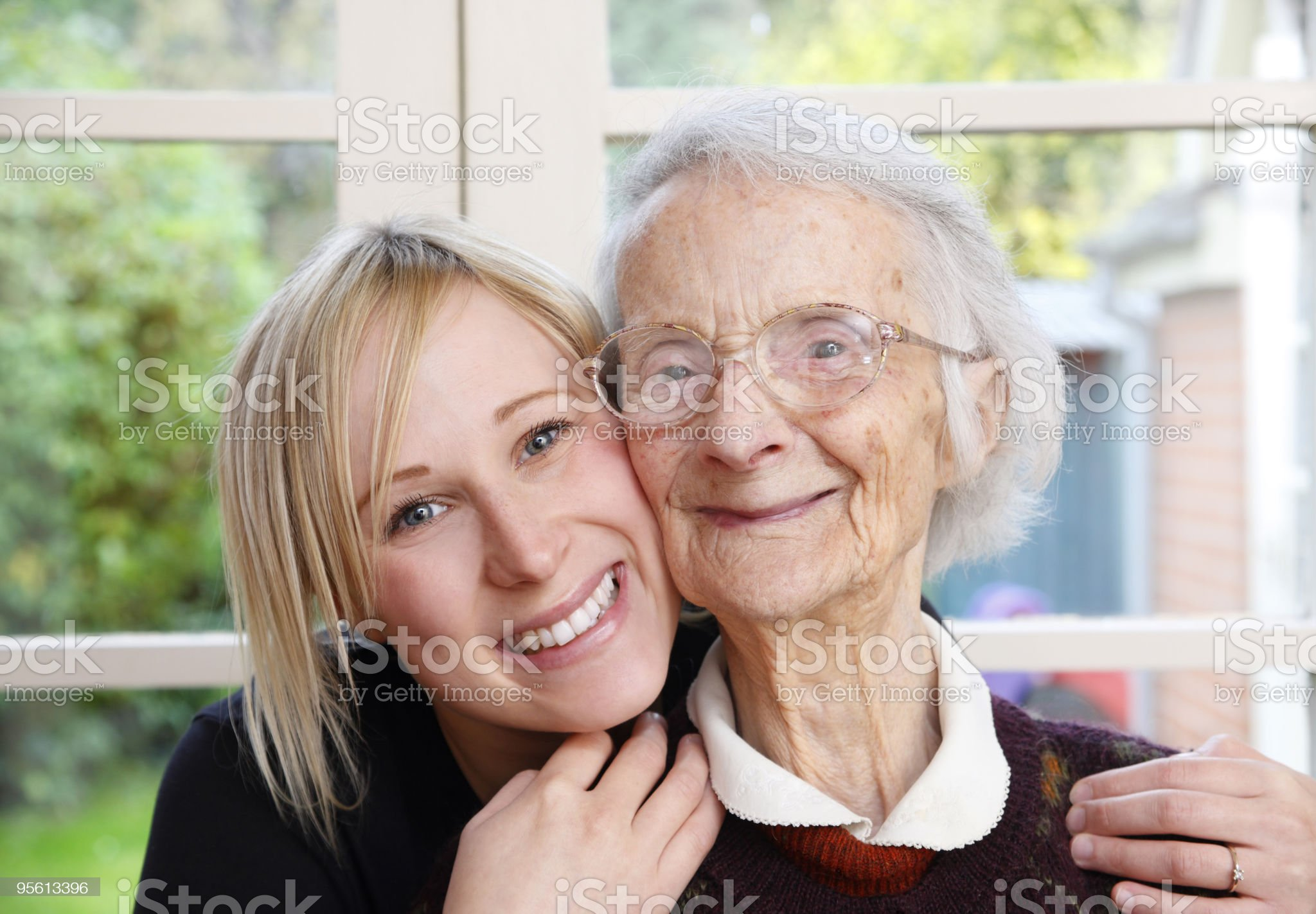 Closeup of young woman hugging her grandmother royalty-free stock photo