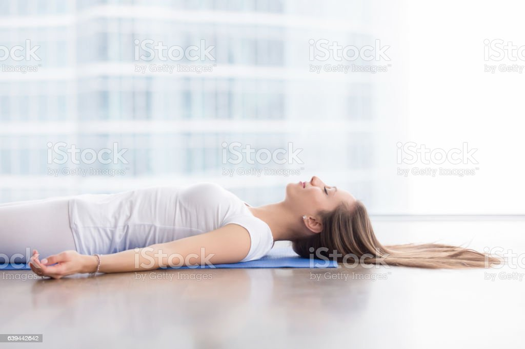 Closeup of young woman in Savasana pose against floor window stock photo