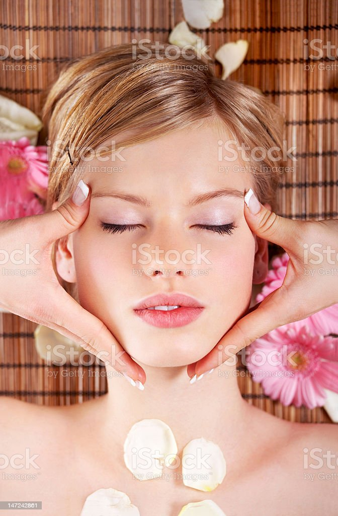Close-up of young woman receiving face massage at day spa royalty-free stock photo
