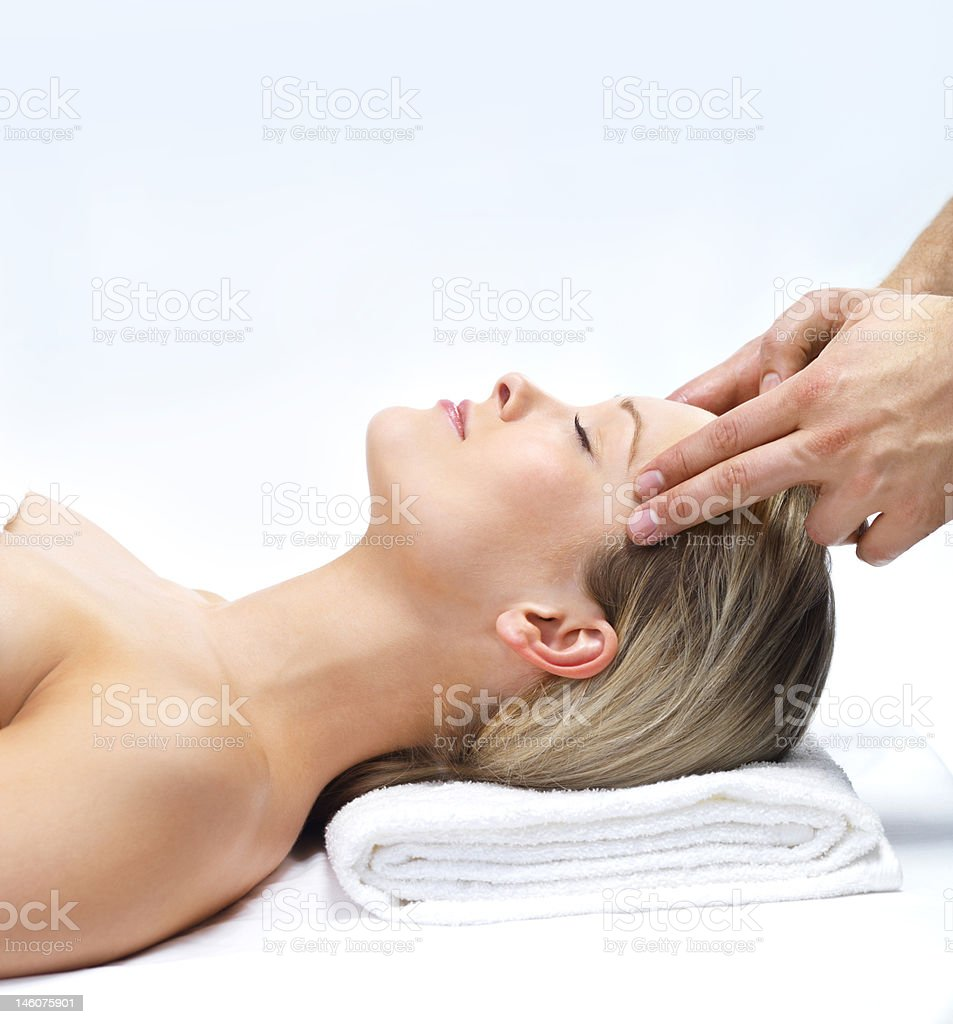 Close-up of young woman receiving facial massage at day spa royalty-free stock photo