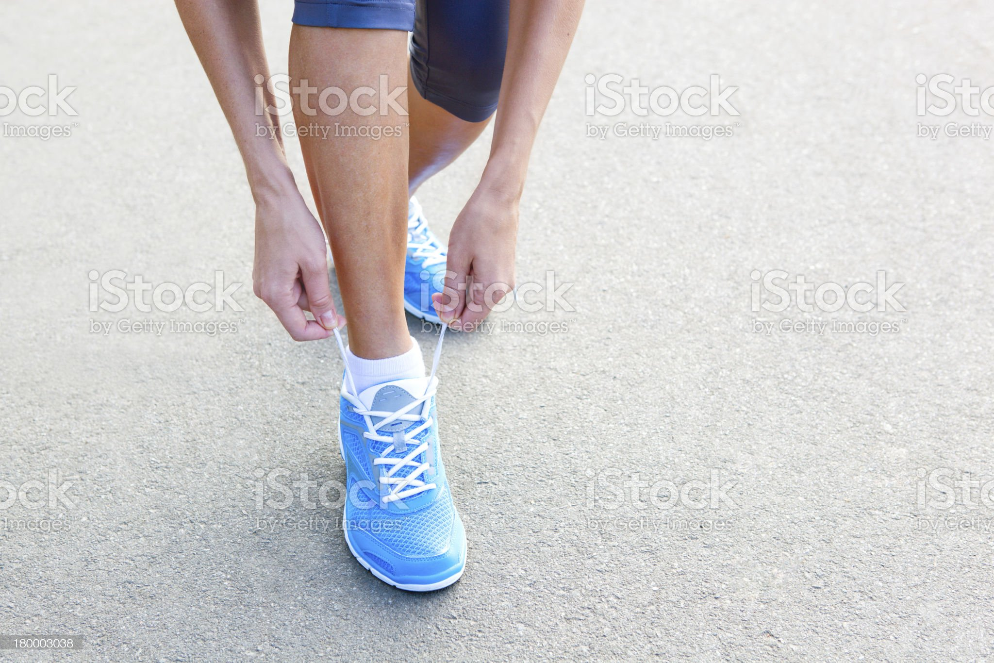 Closeup of Young Woman Tying Sports Shoe. royalty-free stock photo
