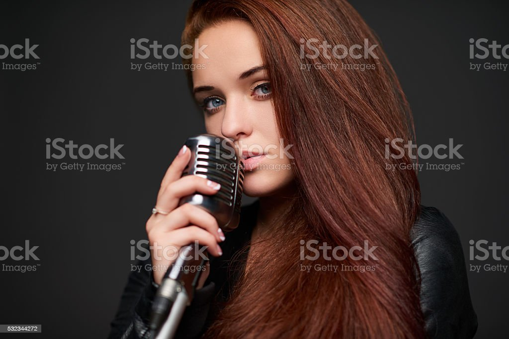 Closeup of young woman with retro microphone stock photo
