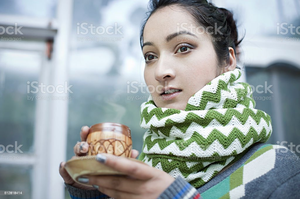 Close-up of young woman with steaming coffee mug in winter. stock photo