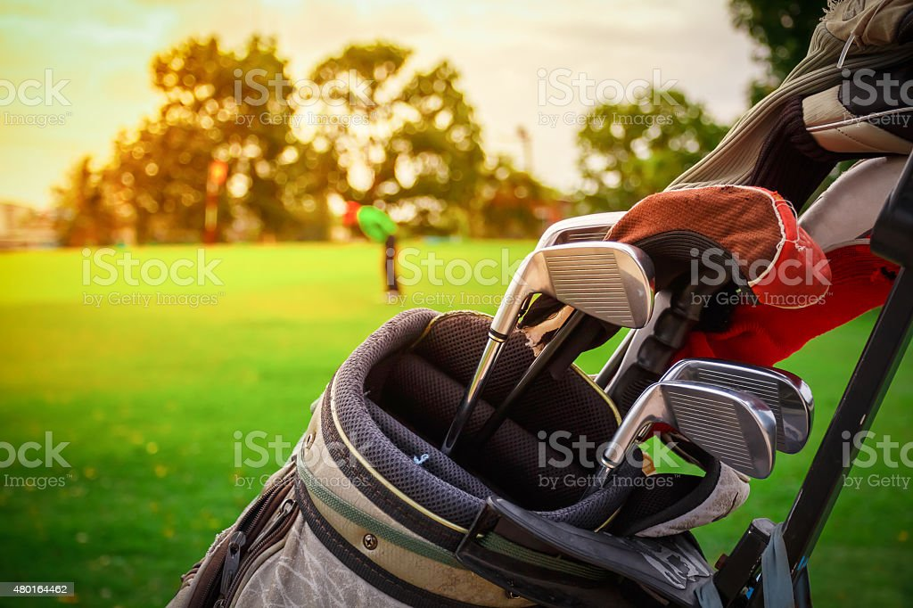 closeup old golf bags on green stock photo