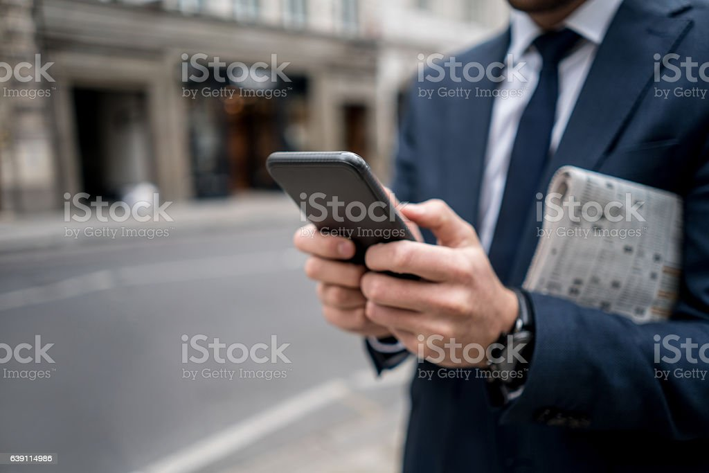 Close-up on a business man texting on the phone stock photo