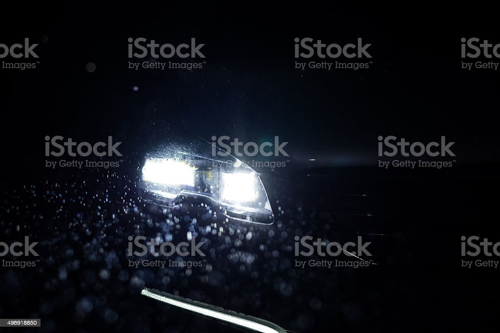 Close-up on a car headlight. Night. Rain stock photo