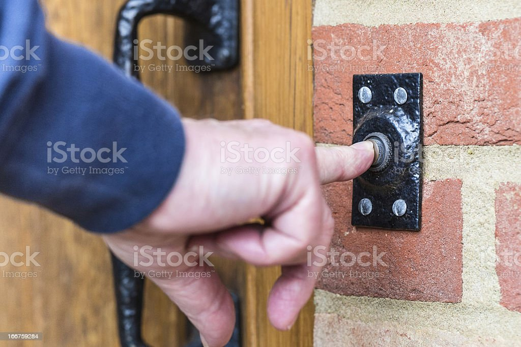 Closeup on a hand pressing a door bell button stock photo